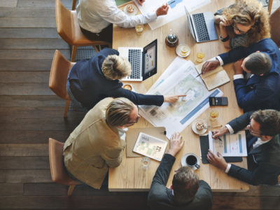 Business leaders discuss strategy around a meeting table.